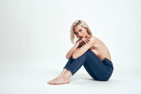 Sensual beauty. Full length of cute young woman in jeans covering breasts with hands and looking at camera while sitting on the floor against grey background in studio