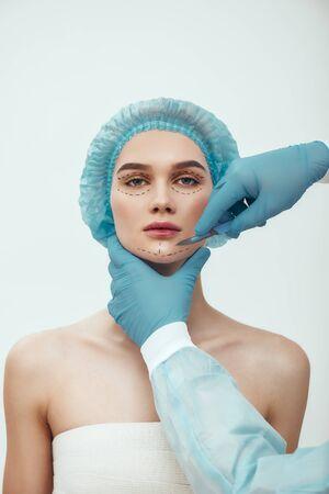 Anti-Aging-Behandlung. Schöne junge Frau im blauen medizinischen Hut mit gestrichelten Linien auf ihrem Gesicht mit kosmetischer Gesichtschirurgie plastischer Chirurgie. Plastischer Chirurg in blauen Handschuhen mit Skalpell