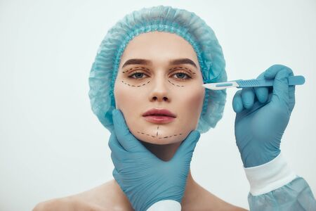 Face lift surgery. Portrait of beautiful young woman in blue medical hat having cosmetic face surgery. Plastic surgeon in blue gloves holding scalpel. Foto de archivo