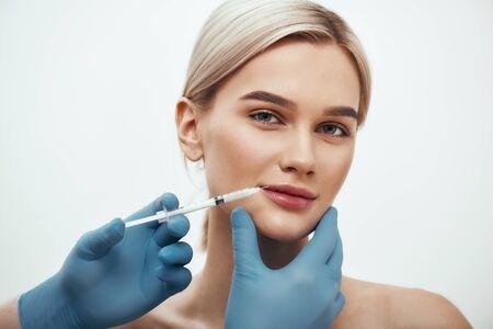 Zastrzyk kosmetyczny. Młoda piękna kobieta patrząca w kamerę i uśmiechająca się, podczas gdy lekarze robią zastrzyk w jej usta