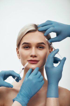 Creating beauty. Portrait of young pretty woman looking at camera and smiling while doctors in blue medical gloves making injections in her face