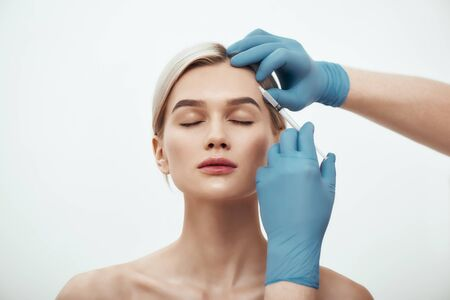 Cosmetic injection. Portrait of young pretty woman keeping eyes closed while doctors hand in blue medical gloves making an injection of botox in her face. Beauty. Facial surgery