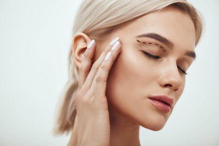 Plastische Chirurgie. Schöne junge blonde Frau, die die Augen geschlossen hält und ihr Gesicht mit einer Skizze darauf berührt Standard-Bild