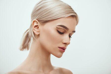 Prima della chirurgia facciale. Vista laterale di una bella giovane donna bionda con uno schizzo sul viso in piedi su sfondo grigio