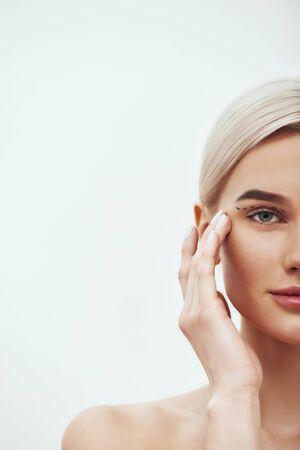 Operacja chirurgii plastycznej. Przycięte zdjęcie ładnej i młodej kobiety blondynka dotyka jej twarzy z czarnymi liniami chirurgicznymi na powiekach i patrząc na kamery. Pojęcie piękna. Modernizacja. Operacja plastyczna