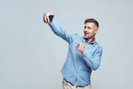 Smile! Cheerful and happy bearded man in casual wear making selfie and gesturing while standing against grey