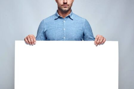 Your text here. Cropped photo of handsome bearded man in casual clothes holding empty blank board while standing against grey background. Advertising