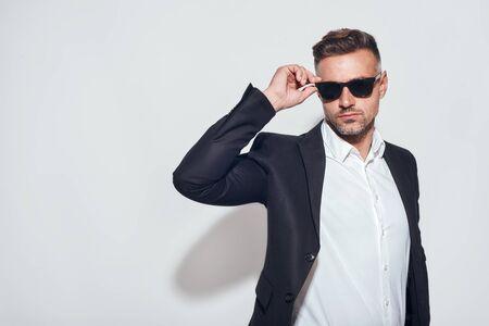 Good looking bearded businessman in classic suit adjusting eyewear while standing against grey