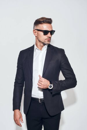Good looking bearded businessman in classic suit and eyewear adjusting jacket and looking away while standing against grey