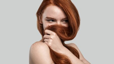 Portrait of young and gorgeous redhead woman playing with her long hair while standing against grey 版權商用圖片