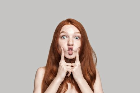 Like a child. Happy young redhead woman making crazy face and grimacing while standing against grey background Standard-Bild
