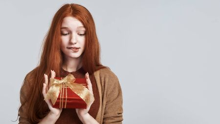 What is inside Portrait of cute and intrigued redhead woman holding gift box and looking at it while standing against grey background
