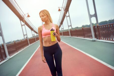 Little break. Portrait of young and active blonde woman with perfect body in sportswear holding bottle of water while standing outdoors on the bridge in the morning