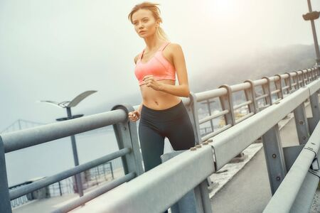 Run for health. Side view of cute and confdent blonde woman in sports clothing jogging on the bridge Banco de Imagens