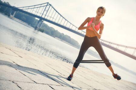 Allenamento sportivo. Giovane e forte donna bionda in abbigliamento sportivo che si esercita con una banda di resistenza all'aperto di fronte al fiume