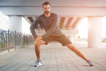 Life is a sport Full-length of young and confident bearded man in sportswear stretching his leg while standing outdoors