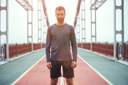 Confident sportsman. Portrait of young and handsome bearded man in sports clothing standing on the bridge and looking at camera Stock Photo