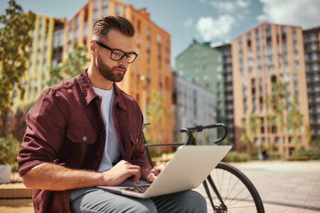I can work from anywhere. Young handsome man with stubble in casual clothes and eyeglasses working on laptop while sitting on the bench near his bicycle Stok Fotoğraf