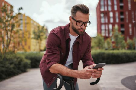I am always in touch. Handsome man with stubble in casual clothes and eyeglasses leaning at his bicycle and looking at mobile phone while standing outdoors