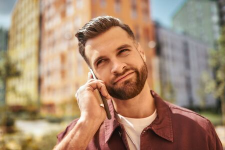I dont know. Portrait of thoughtful bearded man talking by phone while standing on the street Banco de Imagens