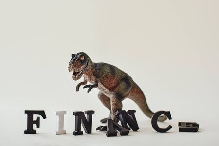 Finance word created with alphabet letters. Dinosaur toy standing in the background