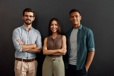 We are great team. Group of three multicultural cheerful young people in casual wear looking at camera with smile while standing against dark background