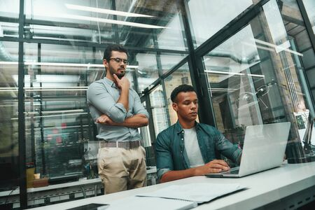 Busy day. Two young and handsome men in casual wear looking at screen of laptop and thinking about new project while working in modern office Stock Photo