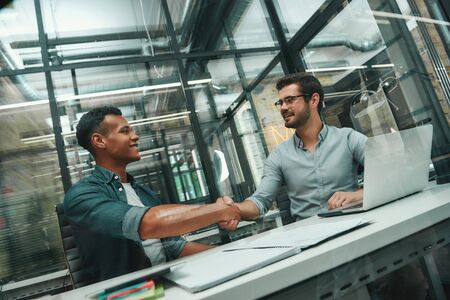 Welcome on board! Two young and handsome men shaking hands and smiling while working in modern office Stock Photo