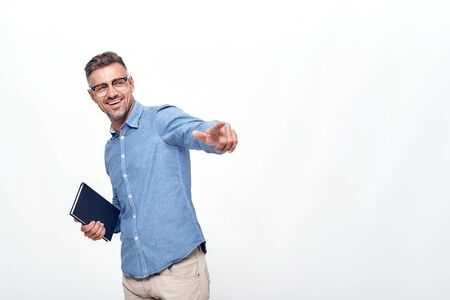 I see you Smiling and handsome man with a stubble in eyewear pointing his finger and holding notebook while standing against grey background Banque d'images - 129158618
