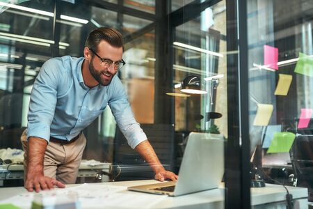 Great results Young bearded businessman in eyeglasses and formal wear looking at laptop and smiling while standing in the modern office Фото со стока