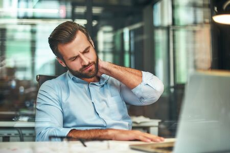 Feeling tired. Young bearded businessman in formal wear massaging his neck while sitting in the modern office