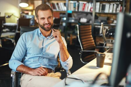 I love my work. Young bearded businessman in formal wear thinking about something and smiling while sitting in modern office
