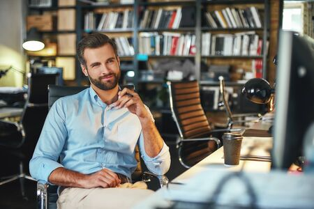 Confident and smart. Young bearded businessman in formal wear thinking about something and smiling while sitting in modern office