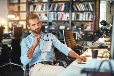 Inspiration. Young bearded businessman holding eyeglasses and thinking about something while sitting in modern office