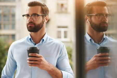 Nice coffee Portrait of young and handsome bearded man in eyeglasses and headphones holding cup of coffee and looking away while standing at the office balcony