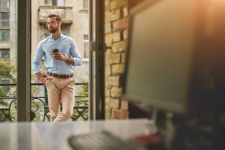 Having coffee break. Young and handsome bearded man in eyeglasses and formal wear holding cup of coffee and looking away while standing at the office balcony