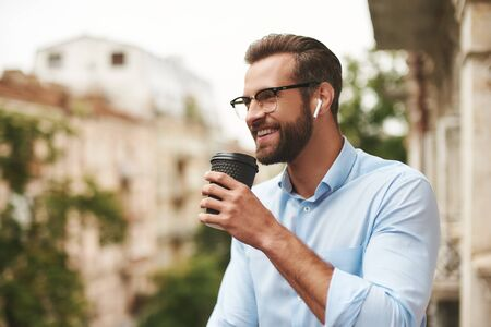 Positive news. Young and handsome bearded man in eyeglasses and headphones holding cup of coffee and talking with friend while standing at the office balcony Stockfoto