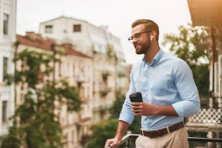 Good news. Young and handsome bearded man in eyeglasses and headphones holding cup of coffee and talking with friend while standing at the office balcony