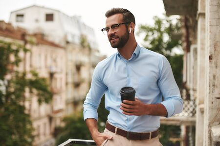 Nice talk. Young and handsome bearded man in eyeglasses and headphones holding cup of coffee and talking with friend while standing at the office balcony