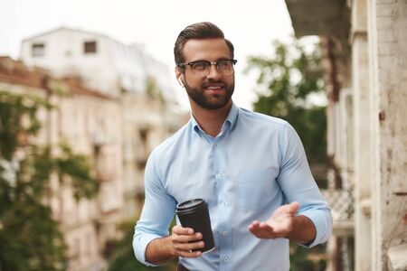 Pause at work. Young and handsome bearded man in eyeglasses and headphones holding cup of coffee and talking with friend while standing at the office balcony