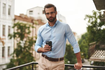 Coffee break. Young and handsome bearded man in eyeglasses and formal wear holding cup of coffee and looking away while standing at the office balcony Stockfoto