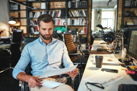 New business strategy. Young and handsome bearded man in formal wear examining documents while sitting in his modern office