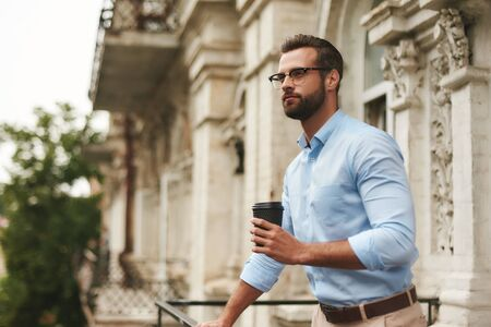 Young and handsome bearded man in eyeglasses and formal wear holding cup of coffee and looking away while standing at the office balcony Stockfoto