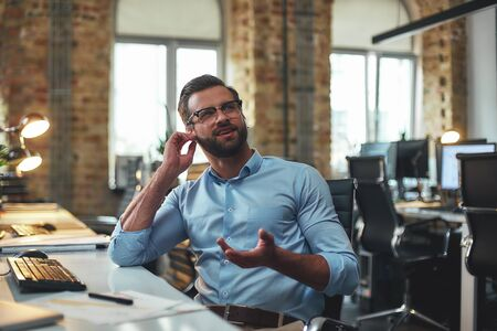 I dont hear you. Portrait of young bearded man in eyeglasses and headphones talking with client while sitting in the modern office