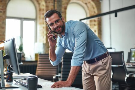 Business talk. Portrait of young and cheerful bearded man in eyeglasses talking on smart phone and using computer while standing in the modern office