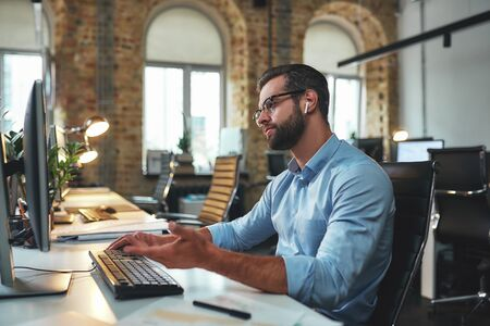 I dont understand. Side view of young and successful bearded man in eyeglasses and headphones typing something on computer and gesturing while sitting in the modern office