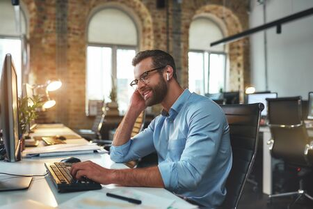 Great results. Side view of young happy bearded man in eyeglasses and headphones typing something on computer and smiling while sitting in the modern office Stock Photo