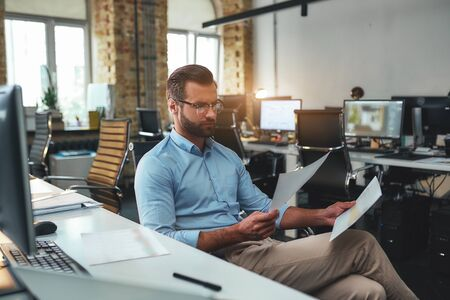 Financial bill. Side view of serious bearded man in eyeglasses and formal wear looking at documents and thinking while sitting in the modern office Stockfoto