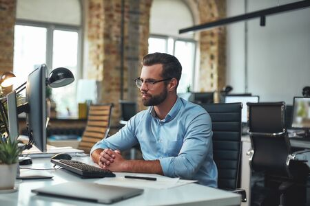 I am so busy today. Young andsuccessfulbearded man in eyeglasses and formal wear looking at computer monitor during his working day in modern office