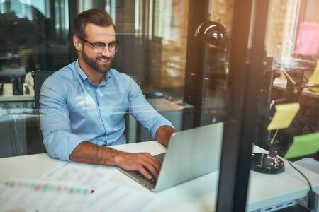 Great results Young bearded businessman in eyeglasses and formal wear looking at laptop and smiling while sitting in the modern office Stock Photo